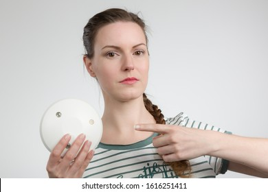 a seriously looking woman shows a smoke detector