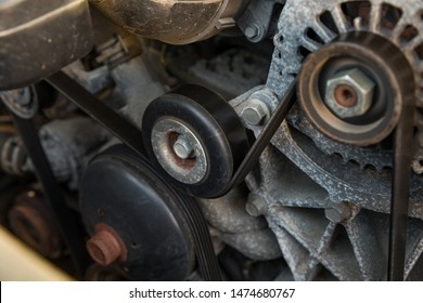 Serpentine drive belt tensioner idler pulley on automobile engine with alternator and water pump pulleys on each side