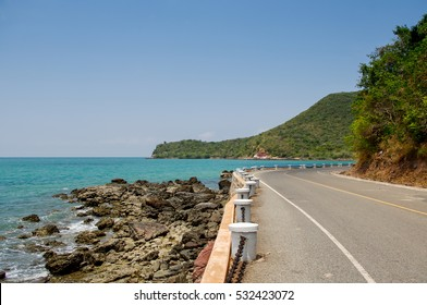 Serpentine road goes down in mountains to Sea in a clear sky sunny day, Thailand.