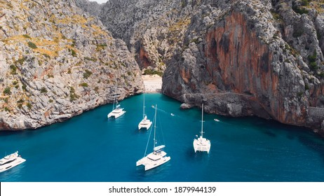 Serra De Tramuntana,Sa Calobra, Torrent De Pareis beach, aerial ,crystal clear water of mediterranean sea with moored sailing boats and yacht going towards the beach. High quality photo