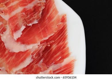 serrano ham plate isolated on black