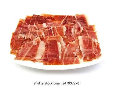 Serrano ham slices on a white dish. Jabugo. Spanish tapa