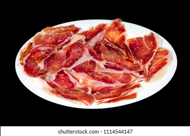 Serrano ham, ham, typical and delicious Spanish food, Isolated background in black. Selective focus foreground