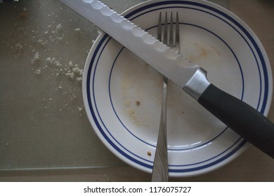 Serrated knife and fork crossed over a greasy plate on top of a cutting board with breadcrumbs.
