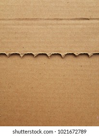 A serrated piece of cardboard on top of another sheet of cardboard as a background with texture
