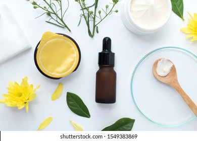 serum bottle with clay mask wooden spoon yellow flowers and serum skincare cream products on white background. Aerial view