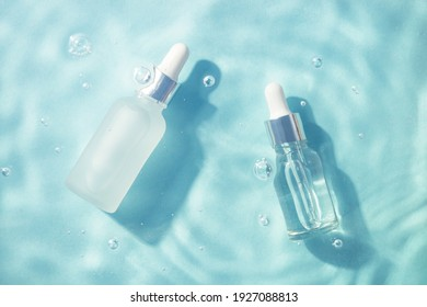 Serum bottles under water. Cosmetic product. Moisturizing, reparing and skincare.