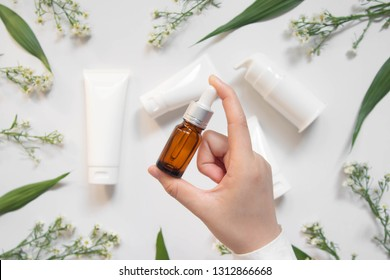 Serum or essential oil w/ organic herbal extract. Woman's hand holding brown glass vial w/ dropper and natural skincare bottles on white background. Natural beauty cosmetic product. Top view.