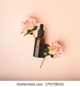 Serum glass bottle with pipette and beautiful flowers on the beige pink background. Natural Organic Spa Cosmetic concept. Front view.