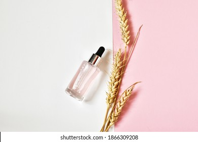 Serum in glass bottle with a pipette with ears of wheat on pink-white background. Concept of natural cosmetic. Moisturizing skincare product. Flat lay, copy space.