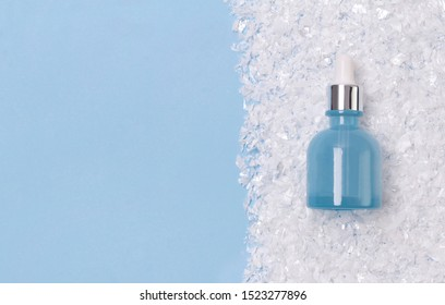 Serum or oil in blue glass bottle with dropper on snowy background. Winter skin treatment concept