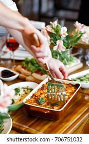 Servant cutting and serving italian lasagna with slotted spatula in a restaurant
