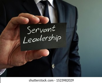Servant leadership concept. Black piece of paper in the hands.