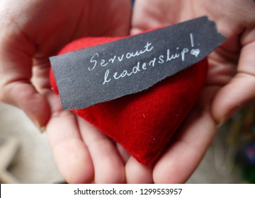 Servant leadership - open hands with red heart and note