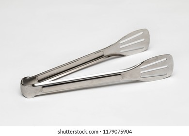 Servants of metal kitchen tongs isolated on white background