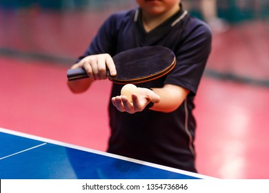 serve the ball in table tennis close, black fitness bracelet on the hand