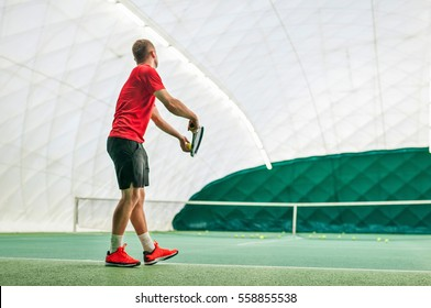 Serve by professional tennis player. Tennis serve indoor of tenis hall. Man on serve with tenis racket and dressed in red t-shirt, black shorts and red shoes.