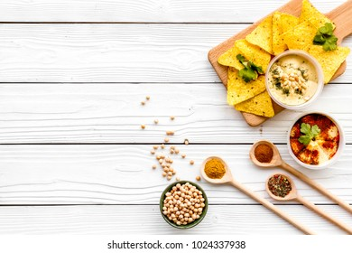 Serve hummus. Bowl with dish near pieces of crispbread on white wooden background top view copy space