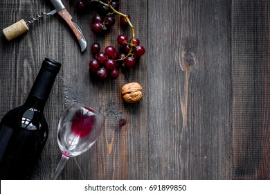 Serve wine. Bottle, glass, nuts and grape on wooden table background top view copyspace