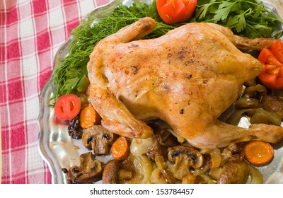 served baked chicken on tray  over checked tablecloth