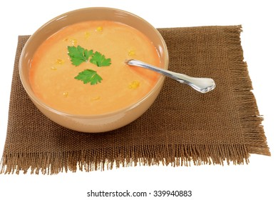 Served in beige bowl over brown placemat cream soup from orange cauliflower seasoned (decorated) with leaf parsley and pieces cauliflower over white background