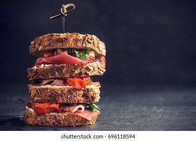 Served big toast sandwich stuffed with cream cheese,prosciutto and grilled tomatoes. Blank space for the ads