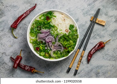 Served bowl of vietnamese soup pho ga with spring onion, chilli peppers and coriander on rustic background
