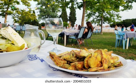 Served delicious Greek traditional food in a restaurant taverna outside. Summer vacation in Chalkidiki, Greece. Fried zucchini, white wine, Greek salad.