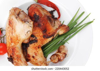 served grilled chicken legs with tomatoes lemon and chives on white plate isolated on white background