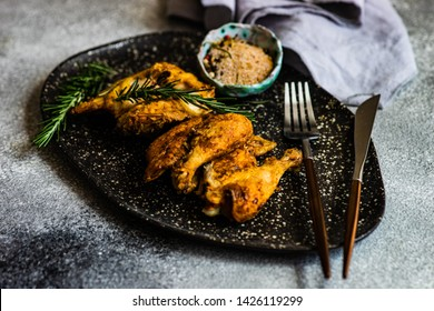 Served grilled chicken with spices and rosemary on stone background with copy space