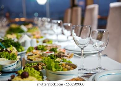 Serviert Ferientisch, Besteck, Geschirr, Brille, Teller, Gabel. Salate und Zahnfleisch. Eine Schüssel mit Löffel, Gabel und Messer auf weißem Tisch. Tischstellung auf weißem Tisch.