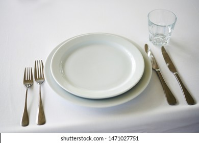 Served long white table with plates and cutlery. Preparing for the banquet, celebration.