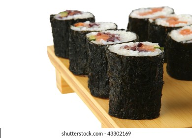 served maki rolls on wooden plate over white