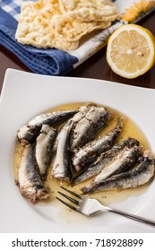 Served marinated sardines in the oil with lemon and corn bread.