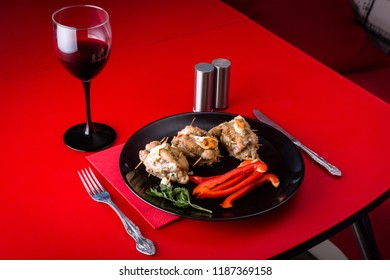 Served meat dish with paprika and salad on a black plate with a glass of wine on a red table