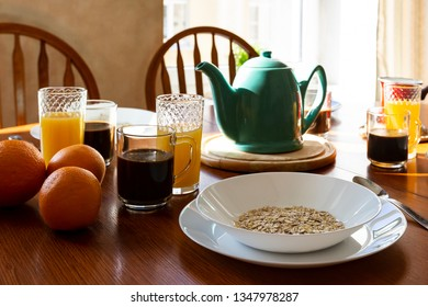 Served morning b&b breakfast on a table: muestli, orange juice, oranges and black coffee