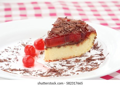 served on white plate slice of delicious cherry cheese cake with cherry topping and decorated with chocolate