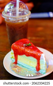 Served piece of rainbow crepe cake with Strawberry Sauce and blackcoffee