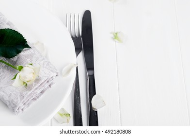 Served plate with napkin and rose on white background
