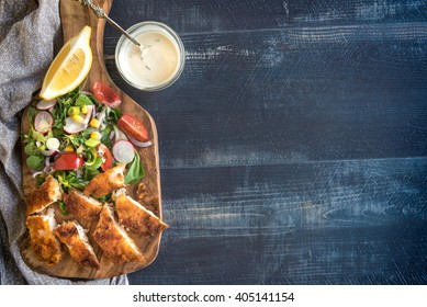 Served sliced catfish fillets with healthy salad on wooden board with blank space