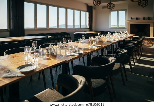Served table with dishes and glasses in tasting room in a winery restaurant. Linear perspective