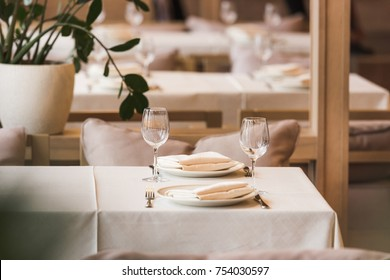 Served table with empty wineglasses and plates for two people