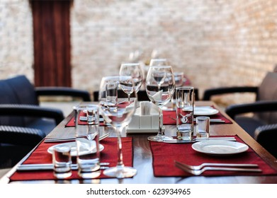 Served table for the event. Lunch in the open air. Summer terrace. Dinner. Wine glasses stand in a row