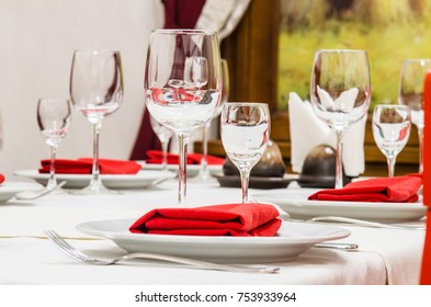 Served table with glasses, cutlery and napkins
