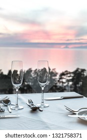 Served table with glasses at sunset. Romantic date by the sea