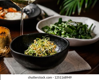Served table with healthy dishes and white wine. Sprouting legumes salad in the front