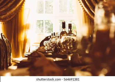 served table on the background of the large French windows with curtains. bottle glasses dishes