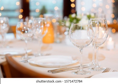 served table on a festive evening with empty plates and glasses against the background of boke