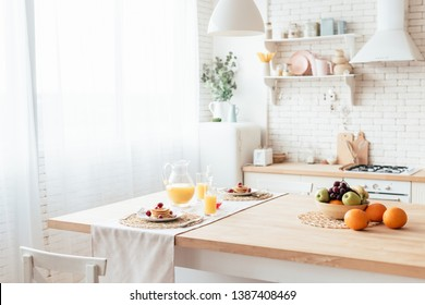 served table with pancakes, fruits and orange juice in kitchen