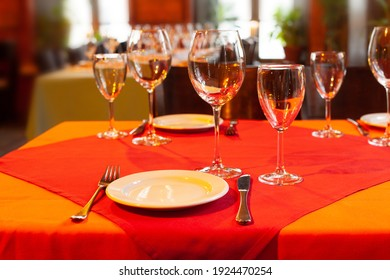 Served table with plate fork knife and beautiful wine glasses on red and orange tablecloths. Soft focus, shallow depth of field background